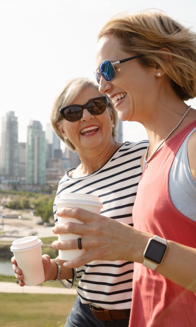 two women with coffee walking together